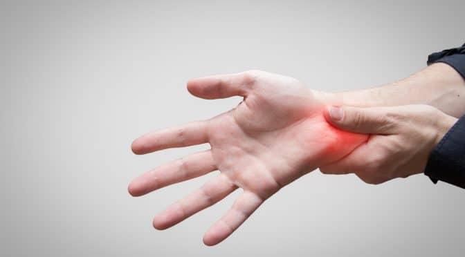Mann hält sein schmerzendes Handgelenk
