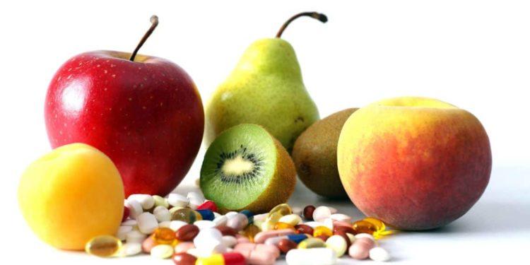 Ein Haufen Vitamintabletten liegt vor verschiedenen Früchten.
