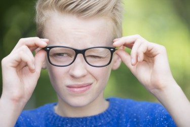 Portrait smart looking blond teenager with glasses and a blink of an eye, thoughtful and clever, outdoor with green blurred background.