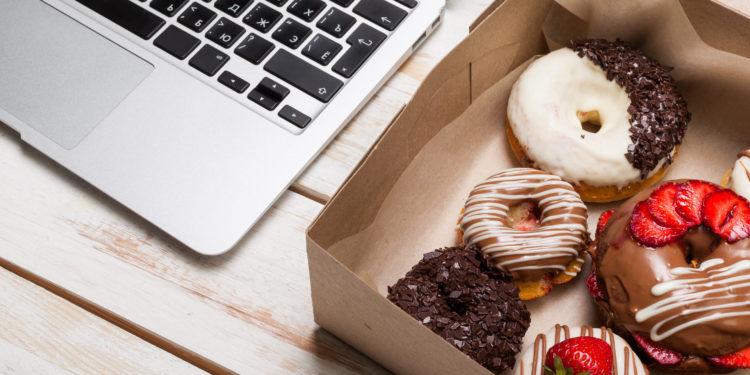 Ein Karton mit Donuts neben einer Tastatur