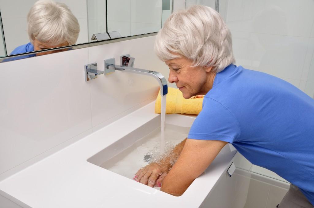 Seniorin macht Wechselbäder im Badezimmerwaschbecken Model released