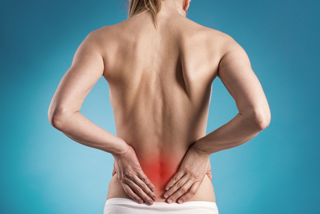 Muscle cramp or backache on naked woman's back