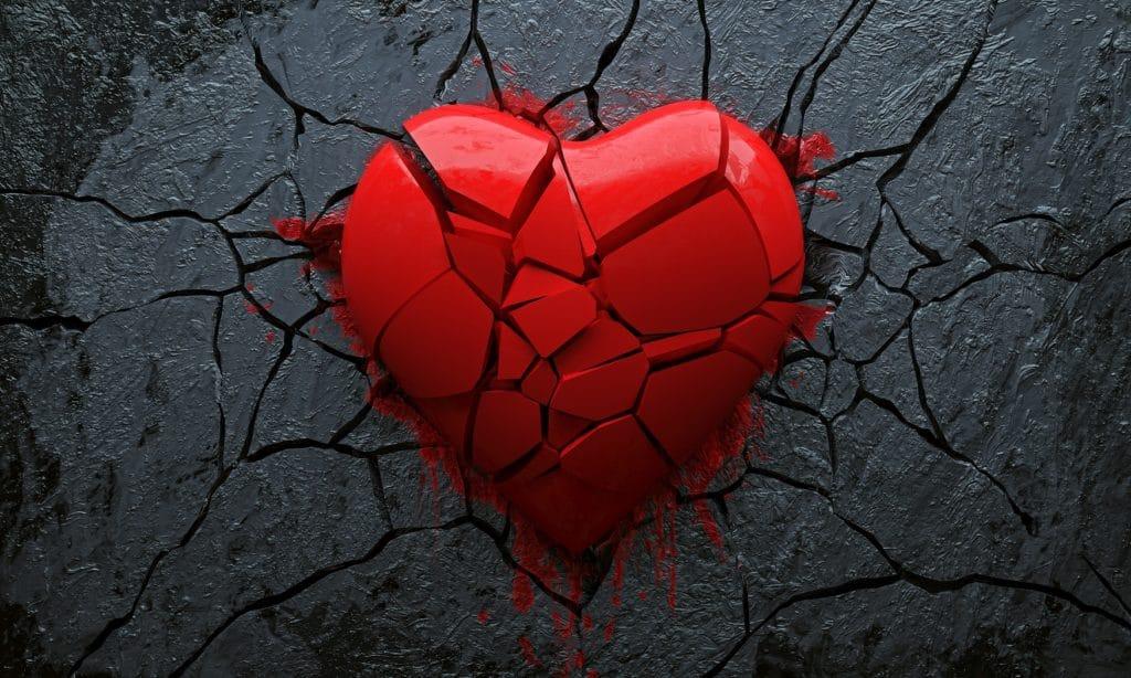 Ein kleine Teile zersprungenes rotes Herz auf schwarzem Hintergrund.