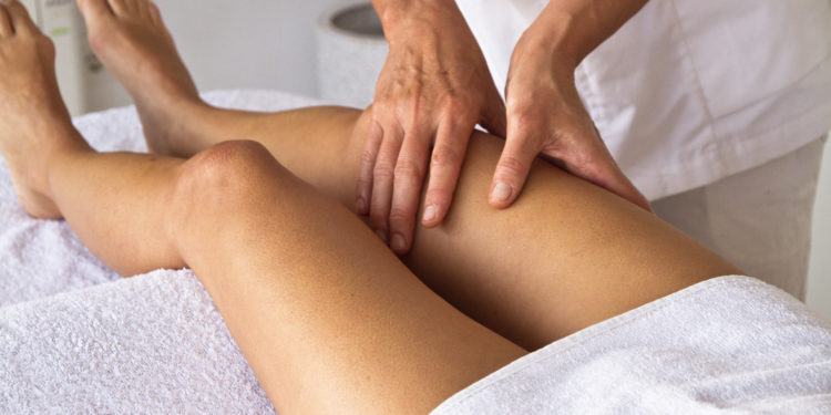 Physiotherapeut behandelt Frau am Oberschenkel.