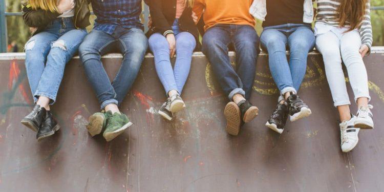 Jugendliche sitzen nebeneinander auf einer Mauer.
