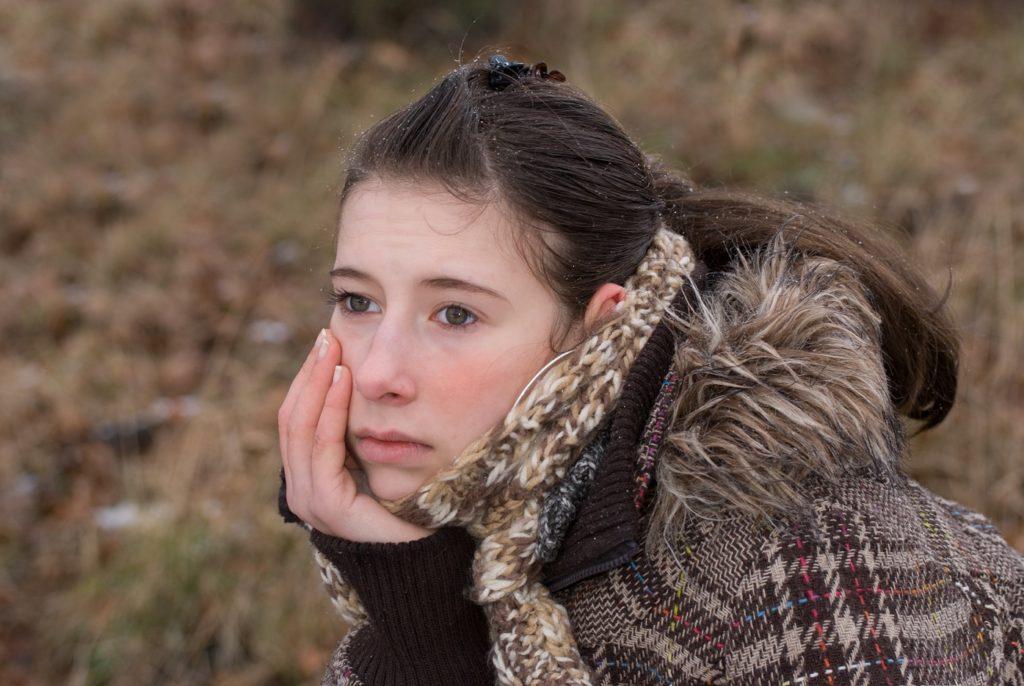 Depressive junge Frau in der Natur