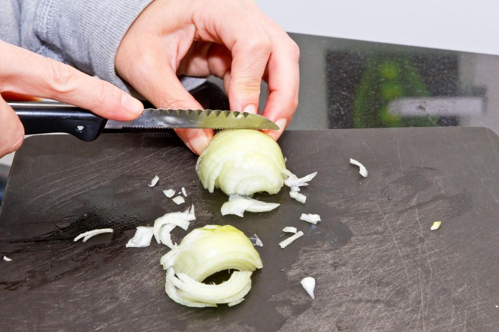 Frau beim Zwiebel schneiden