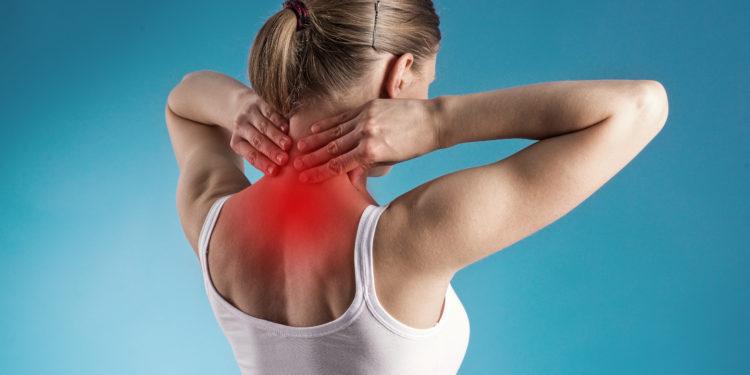 Frau fasst sich mit beiden Händen an den schmerzenden Nacken.