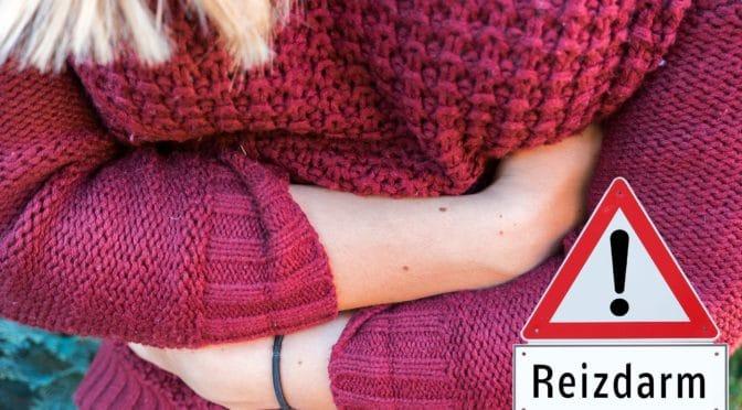 Eine Frau mit Bauchschmerzen hält sich die Arme schützend vor den Bauch.