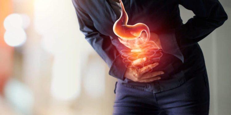 Eine Person hält in gekrümmter Haltung die Hände vor den Bauch.