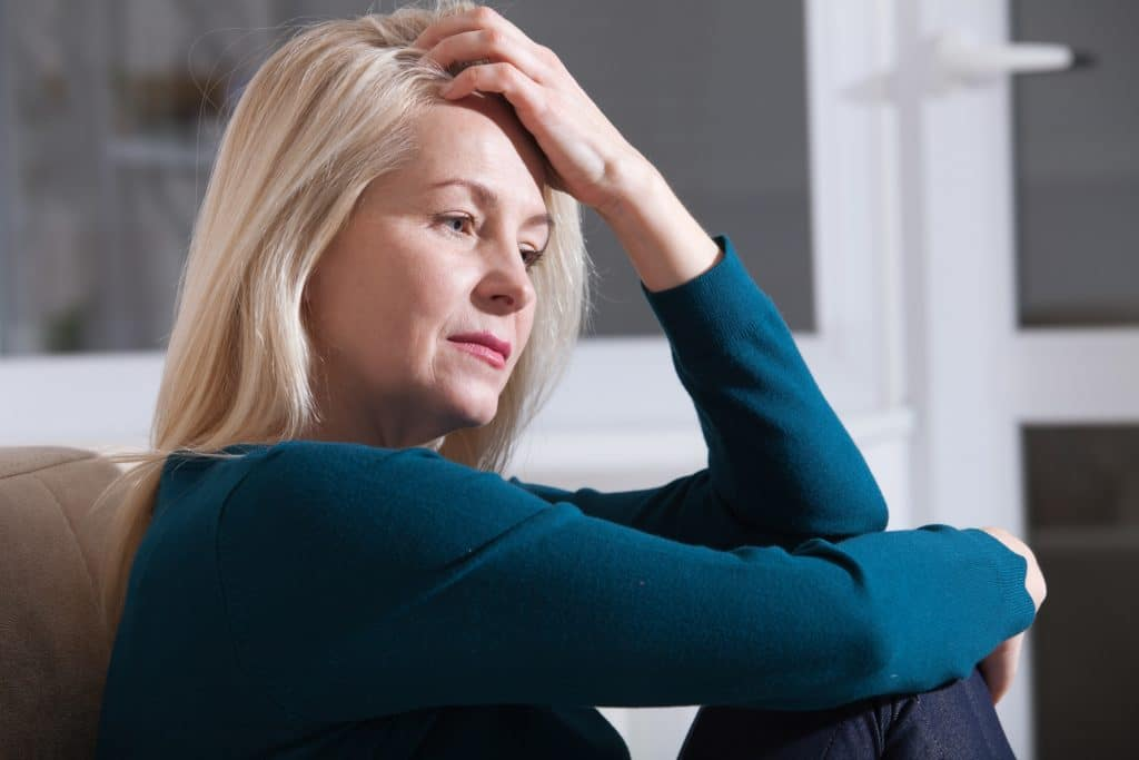 Frau guckt traurig und fasst sich ins Haar.