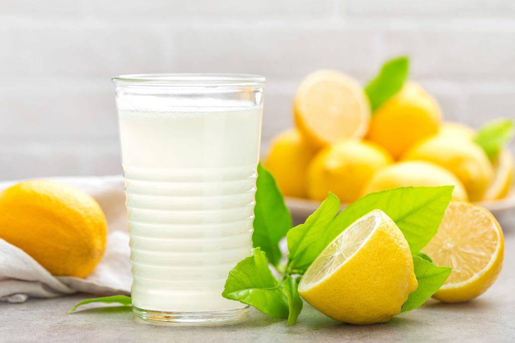 Frische Zitronen und ein Glas Zitronensaft