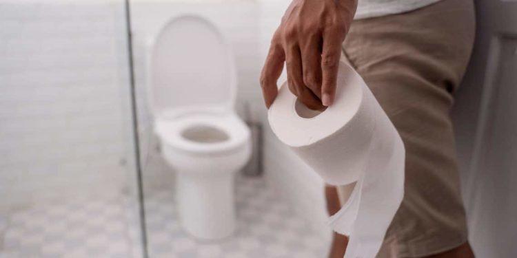 Mann geht mit Kloppapierrolle in Richtung Toilette.