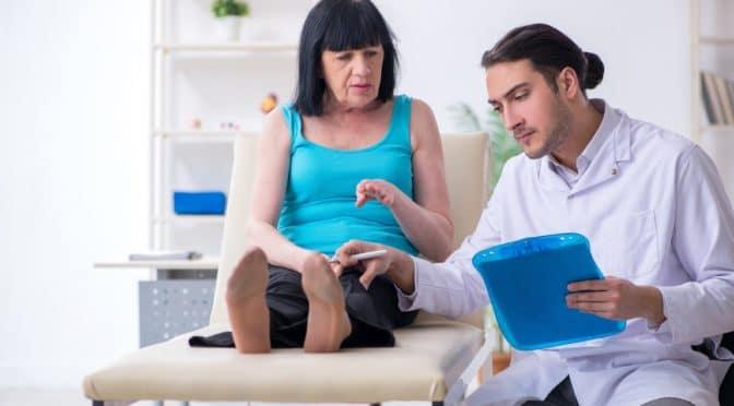 Ein Arzt untersucht die Beine einer Patientin.