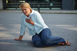 Atmenlose Frau sitzt erschöpft auf dem Bürgersteig