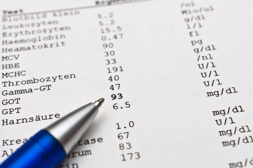 Stift deutet auf einer Liste von Blutwerten auf erhöhte Lebwerten.