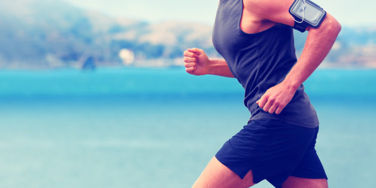 Mann mit Pulsmessgerät am Arm joggt am Meer