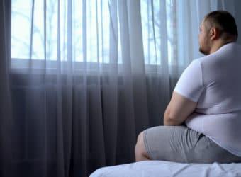 Ein übergewichtiger Mann sitzt auf einem Bett.