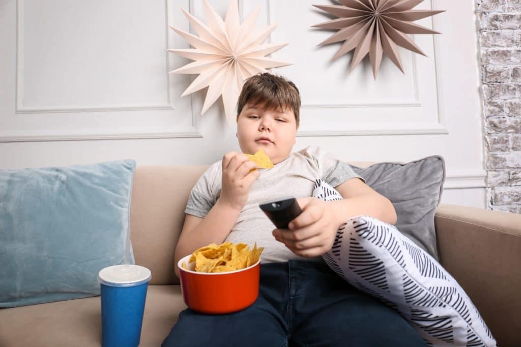 Ein Junge sitzt vorm Fernseher, isst Chips und trinkt Cola.