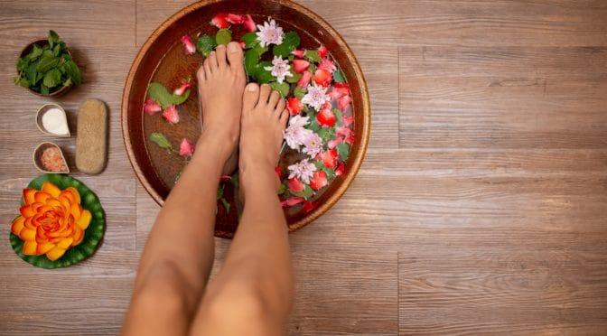 Füße einer Frau in Schale mit Wasser und Blüten.