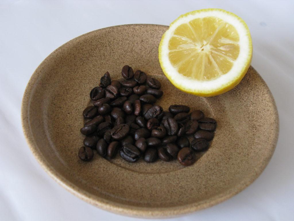 Zitronenscheibe und Kaffeebohnen auf einem Teller