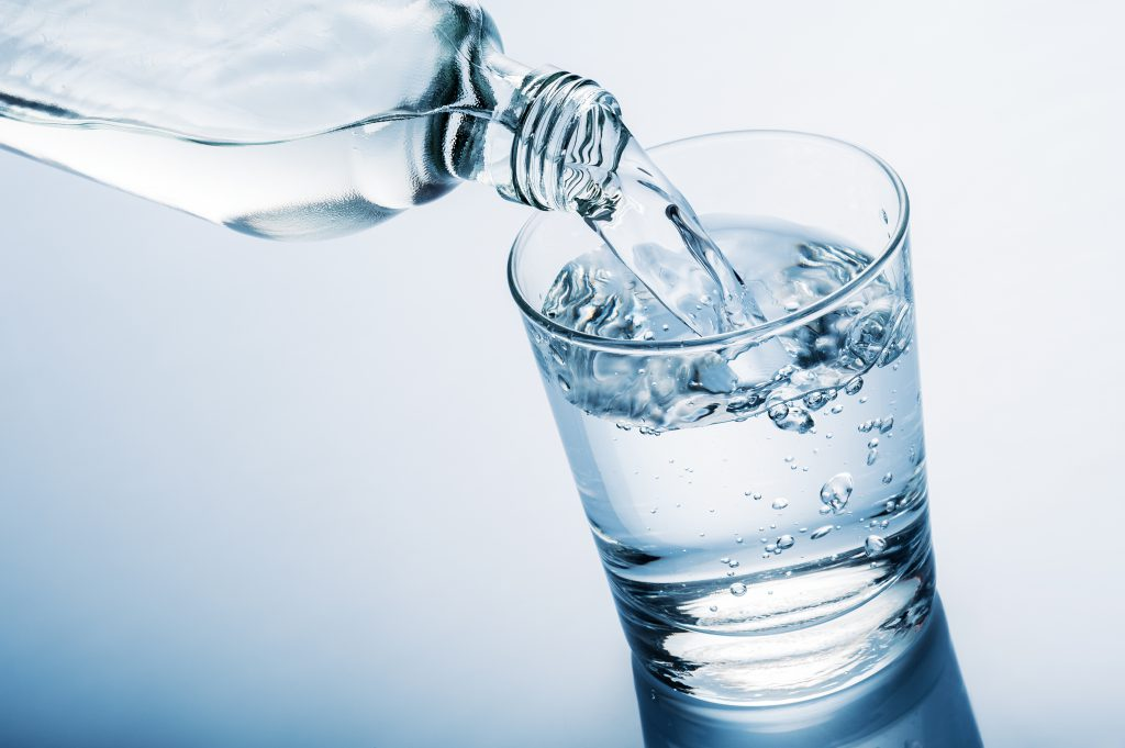 Wasser aus der Flasche in ein Glas eingeschenkt