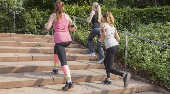 Drei Frauen laufen eine Treppe im Freien hoch