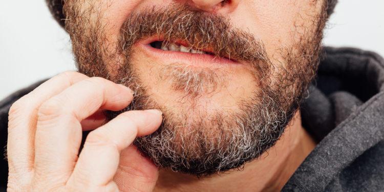 Ein Mann mit Bart kratzt sich im Gesicht