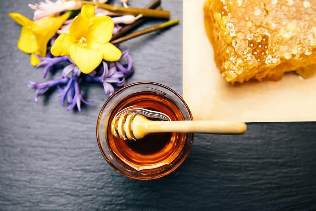 Honig in Glasschale mit Holzlöffel neben Honigwabe und losen Schnittblumen.