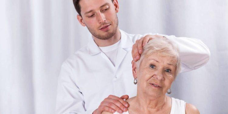 Therapeut behandelt Nackenbereich einer älteren Frau.