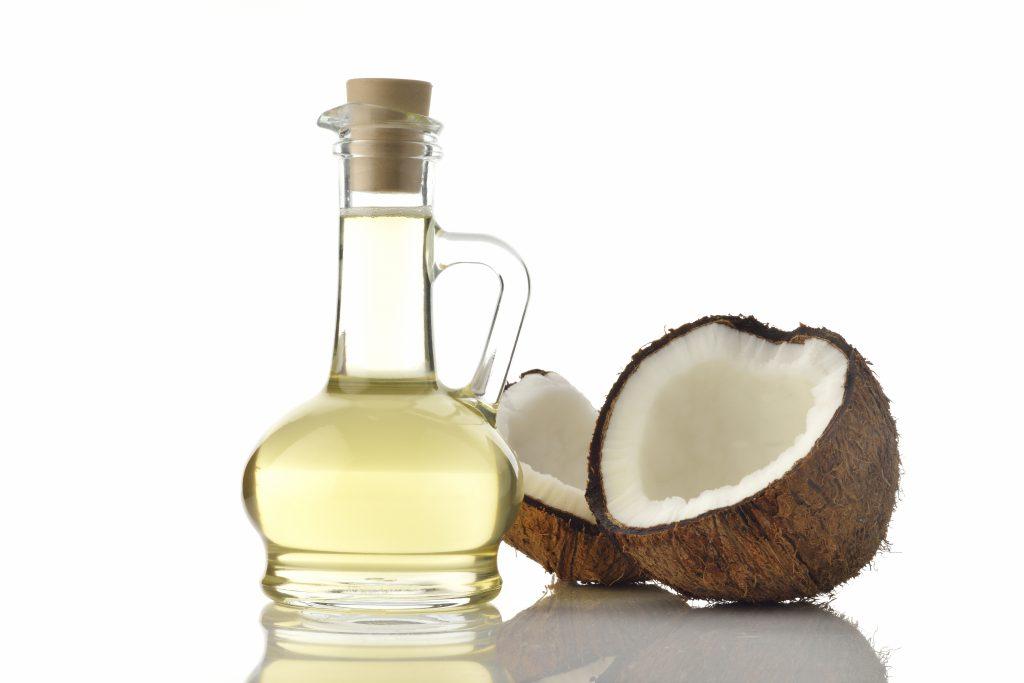 Kokosöl in einer Flasche und Kokosnuss