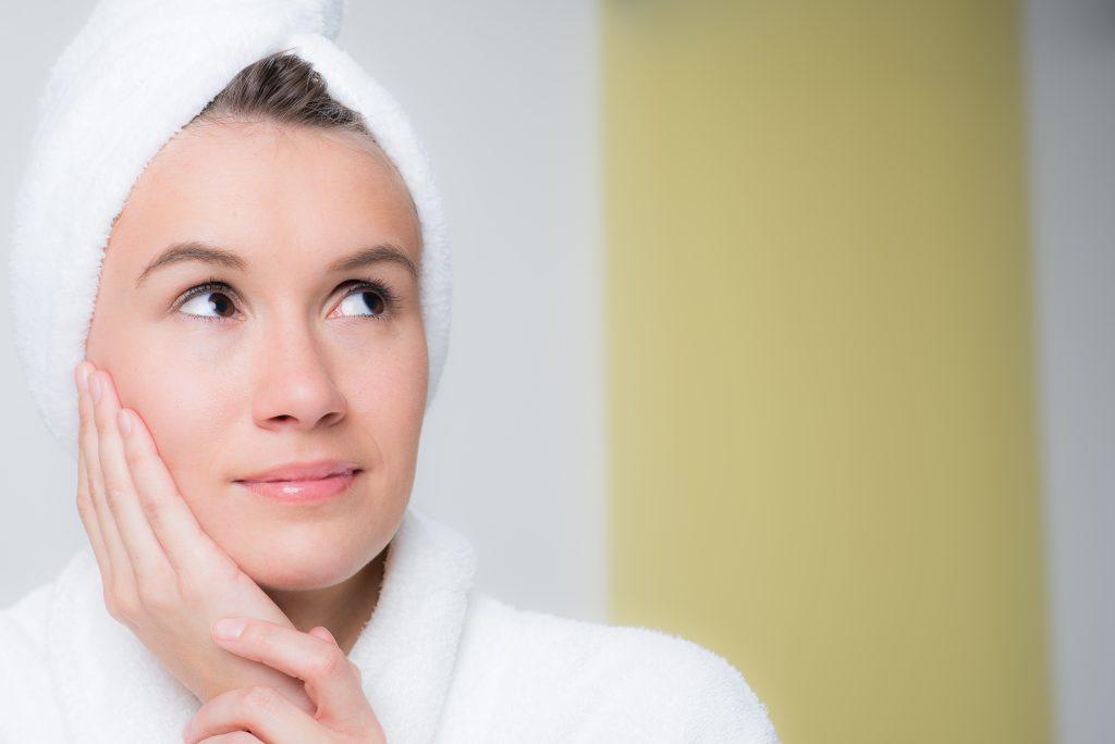 Frau mit Handtuch auf dem Kopf  macht Haarkur