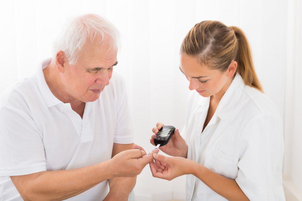 Медицинский работник проводит анализ глюкозы крови у пожилых пациентов