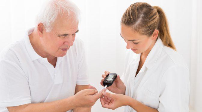 Medizinische Fachkraft führt bei älterem Patienten eine Blutzuckermessung durch