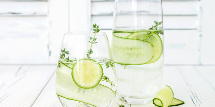 Zwei Gläser Wasser mit Limetten- und Gurkenscheiben
