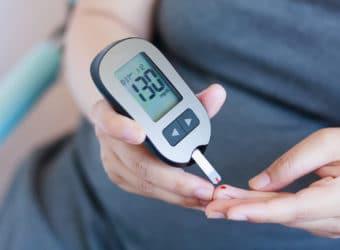 Eine Person überprüft ihren Blutzuckerspiegel mit einem Messgerät.