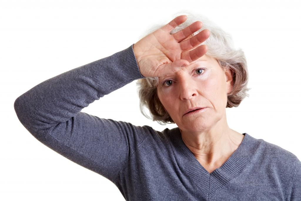 Seniorin hält ihre Hand an die warme Stirn