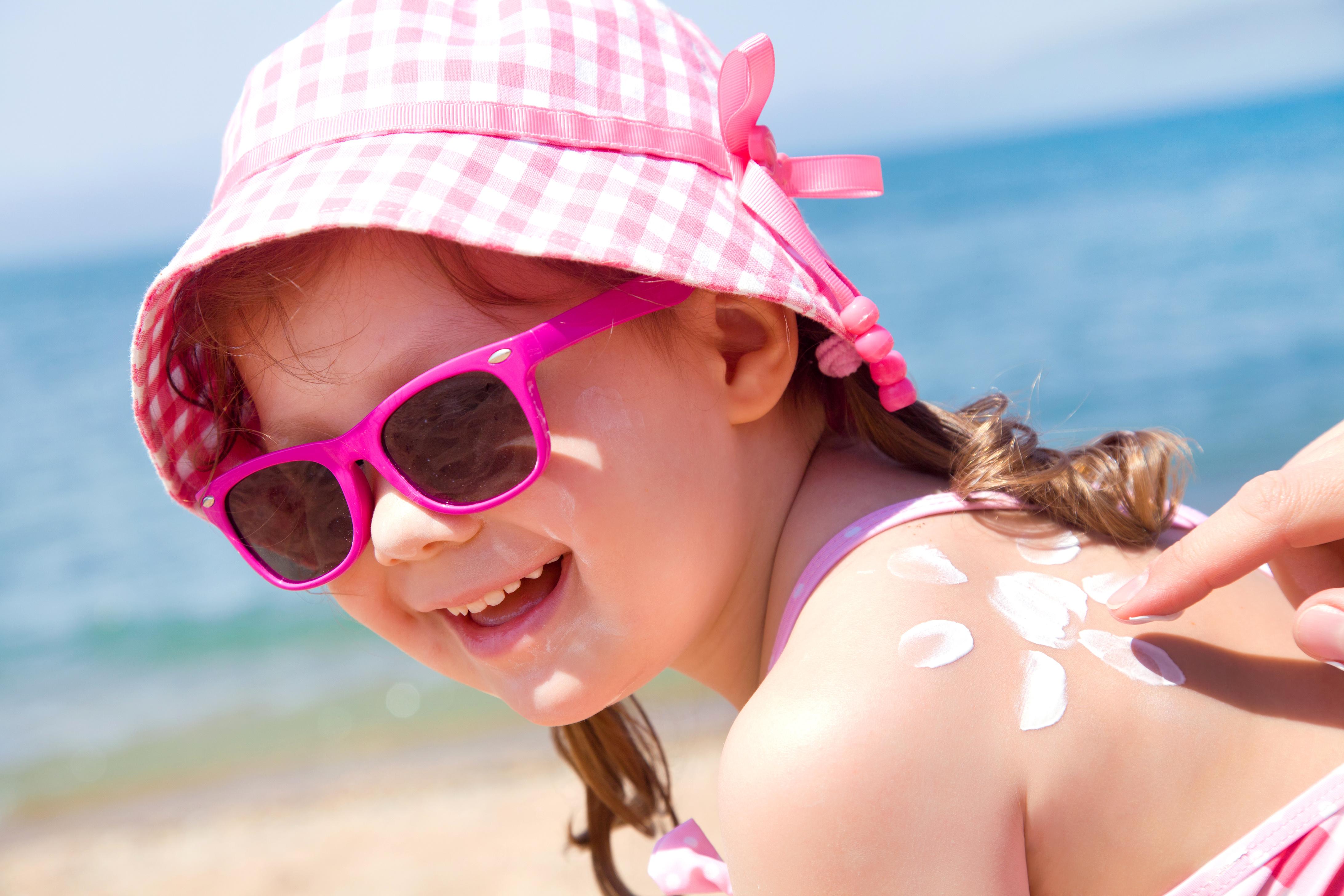 Mom anoints protective cream back a little girl on the beach