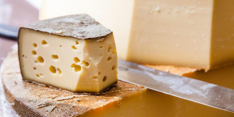 Käse auf einem Holztisch mit einem Messer