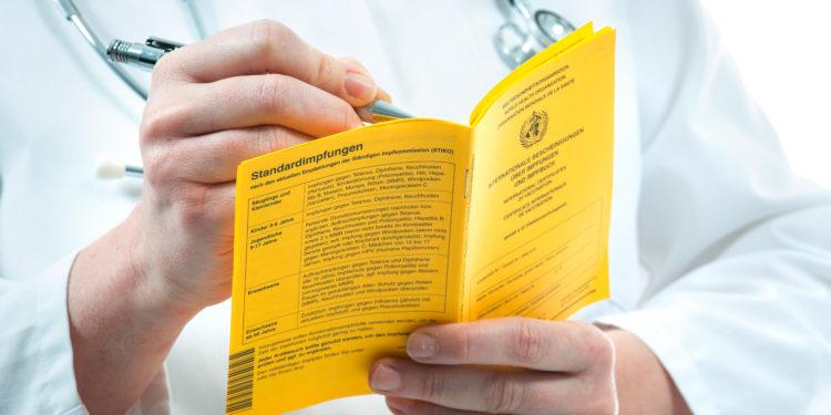 Arzt macht einen Eintrag im gelben Impfpass
