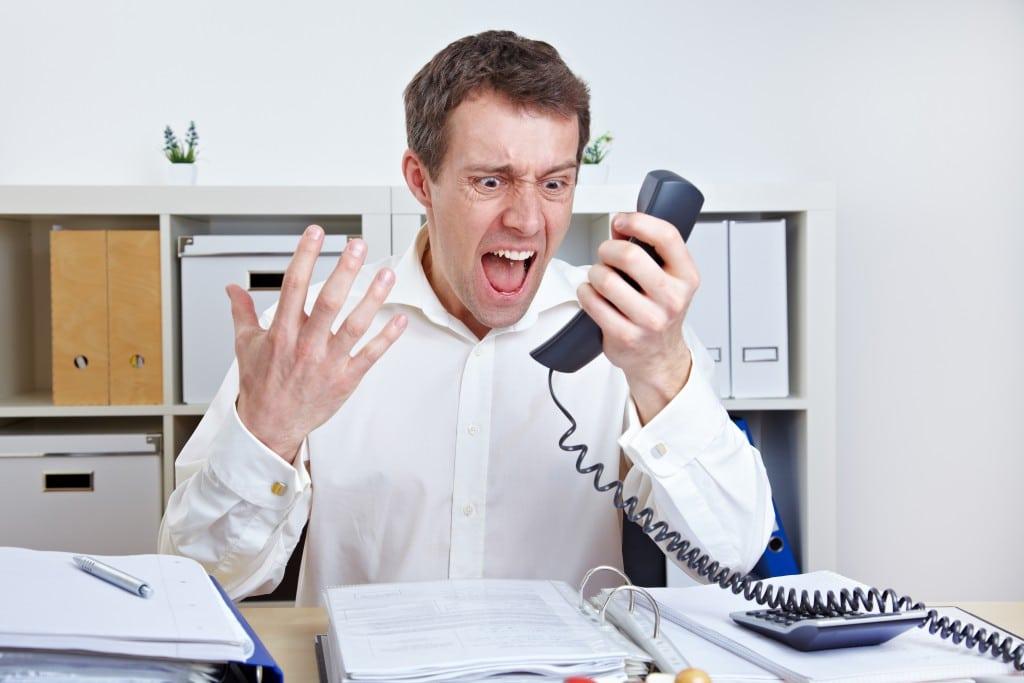 Zorniger Geschäftsmann telefoniert im Büro am Schreibtisch