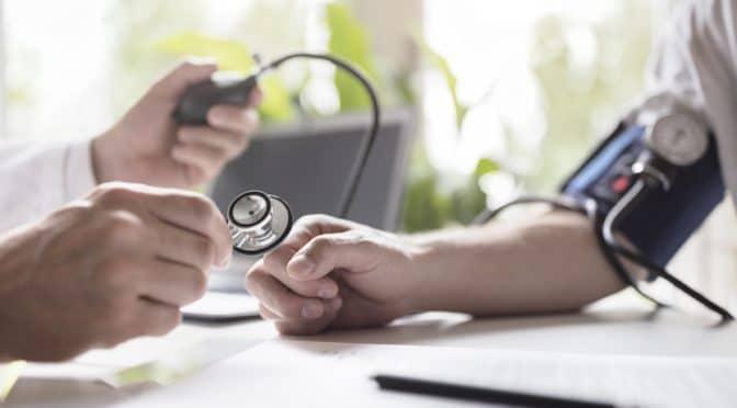Arzt misst den Blutdruck eines Patienten.