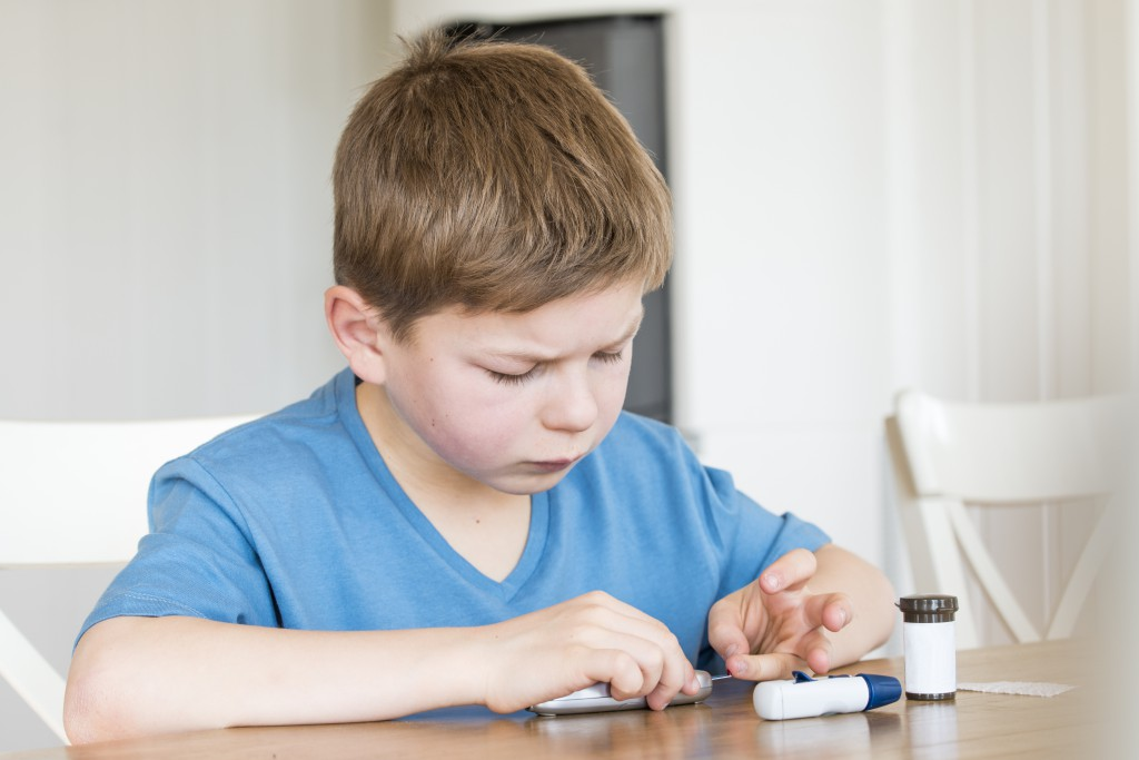 Young boy with diabetes measuring blood sugar.