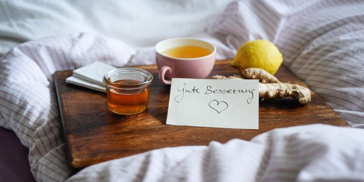 Tee, Zitrone, Ingwer und Honig auf einem Holztablett in einem Bett