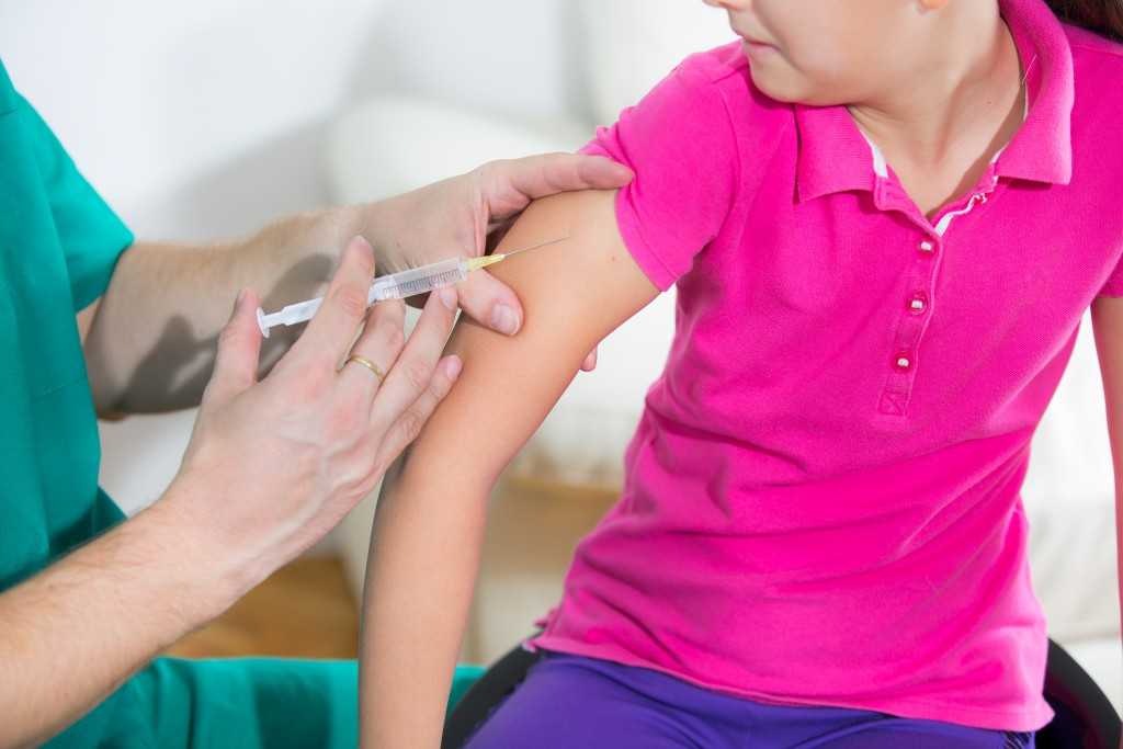Doctor giving vaccination injection to little girl patient