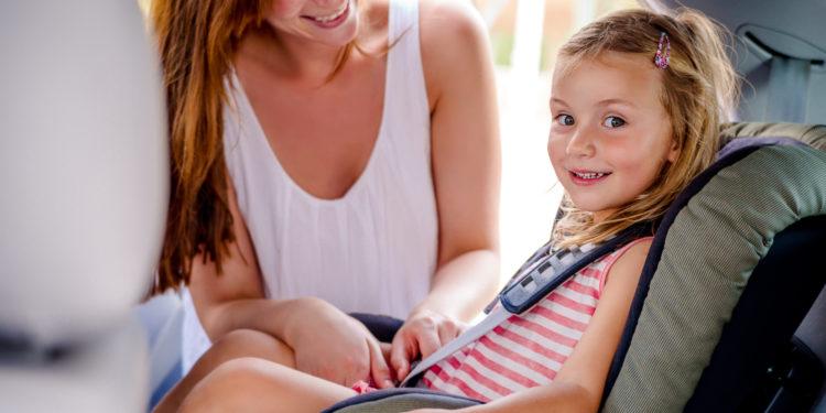 Mutter schnallt ihre Tochter im Auto-Kindersitz an