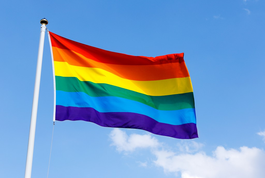 Rainbow flag proudly waving against the blue sunny skies
