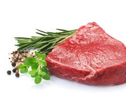 Ein Stück rohes Fleisch mit frischen Kräutern