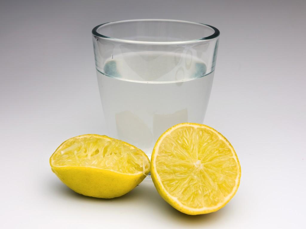 Glas Wasser mit zwei Zitronenhälften