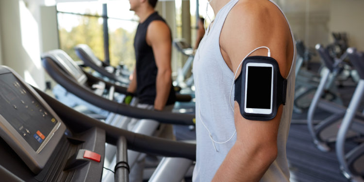 Zwei Männer laufen auf Laufbändern in einem Fitness-Studio.